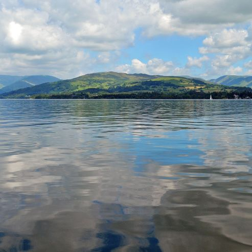 Lake Windermere, seen from a boat. A reflection of the clouds and mountains can be seen on the water. Boats are observable in the water in the far.